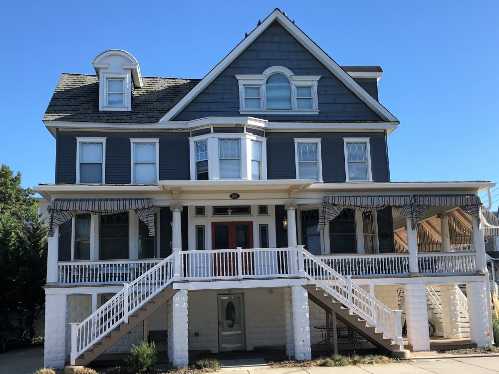 Ocean City vacation rental with Front of Property - Entrance is up the steps.  Red doors