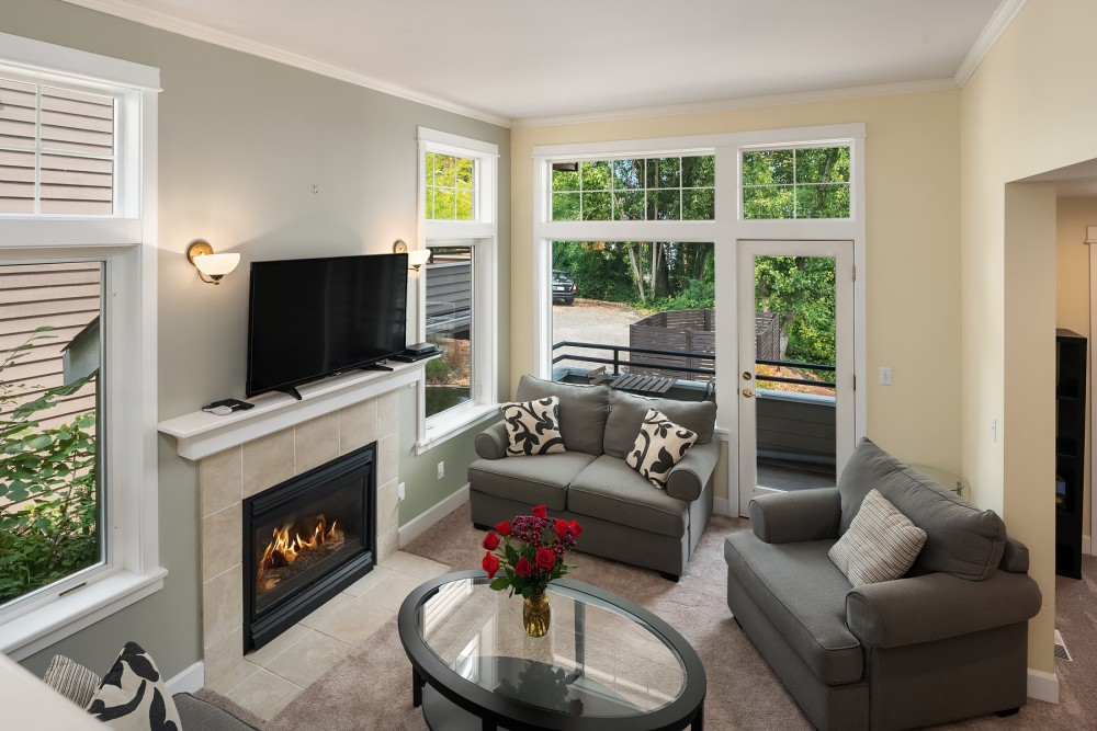 Seattle vacation rental with The living room is furnished with a queen sleeper sofa  love seat  accent chair  and flat screen tv   Enjoy the bright airy room and the gas fireplace
